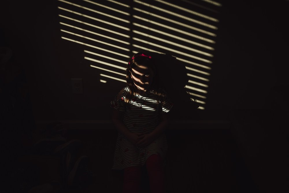 girl sits in shadow on ground in hallway | Whidbey Island family photographer
