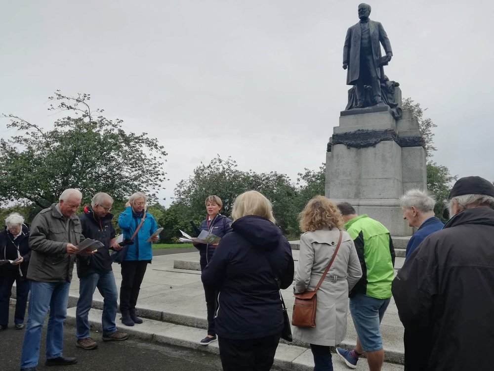 Guide Perri Hopkinson leading the walk under the watchful gaze of Andrew Carnegie