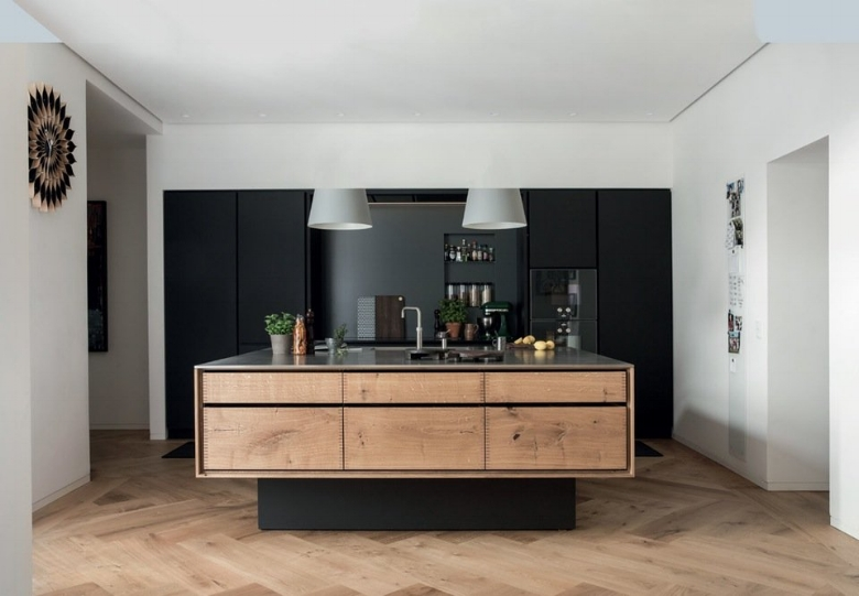 A square peninsula constitutes the kitchen's center. Soren has even drawn the simple lines made of Dinesen planks without handles, which highlights the feel of wood. The tabletop is made of steel, and the rear wall of linoleum with built-in hob and fridge.