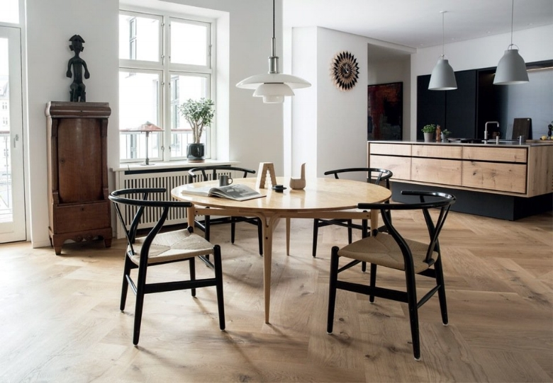 The dining room is decorated with bright, simplistic design and black Wishbone chairs from Hans Wegner gives edge to an inherited Bruno Mathsson table. Poul Henningsen pendant lamp with opal glass shade provides a soft light over the table during meals.