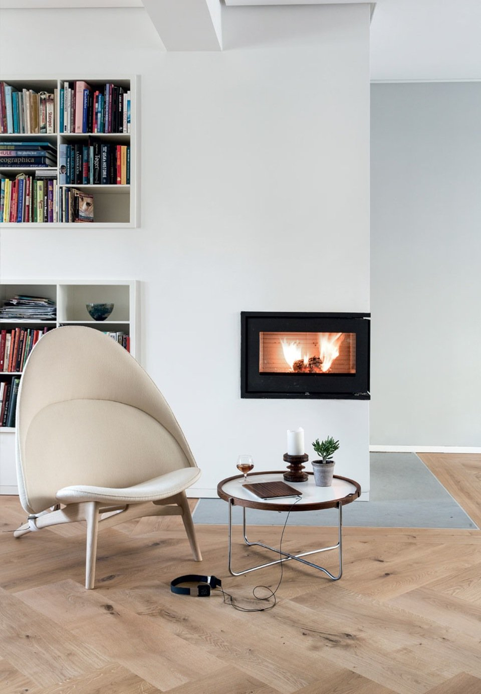 Modern and timeless nook with built-in shelving and Rais fireplace. The chair is the PP 530 Tub Chair by Hans Wegner recently put into production. The domed lines are repeated in the table, also by Hans Wegner, where the wooden frame creates a soft contrast to the metal legs. By mixing woods creates Søren life and warmth in the interior.