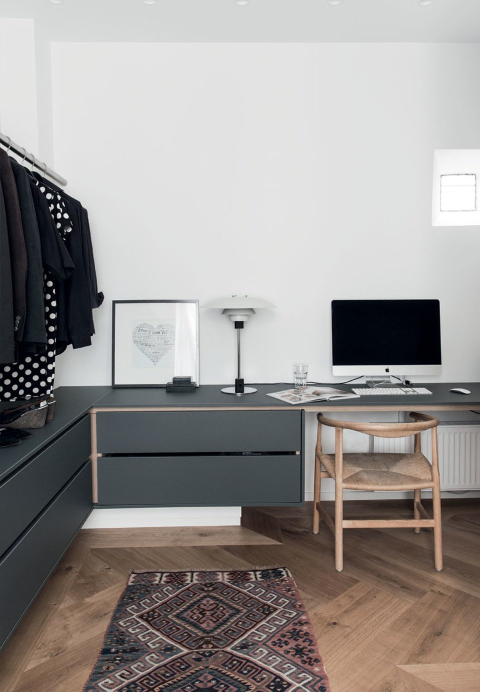 The couple's walk-in closet which is also the office. A bright PP201 Hans Wegner chair is used as office chair, and PH 4/3 lamp by Poul Henningsen tables and drawers in made of linoleum, which lends to a soft subdued look.