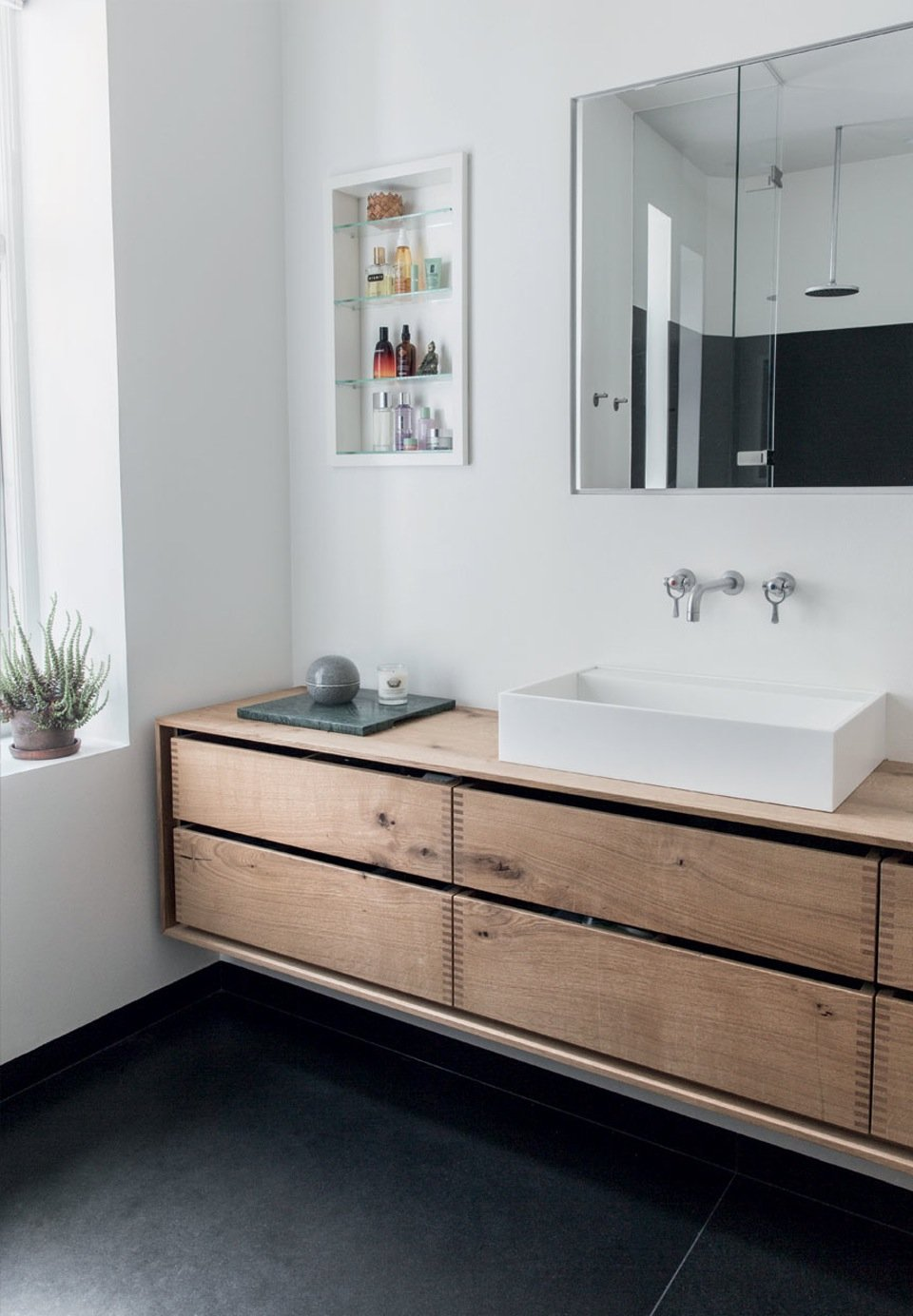 The fittings in the bathroom are made of oak planks treated with natural oil. Two large granites slices constitute the floor, creating at the same time a raw and soft contrast.