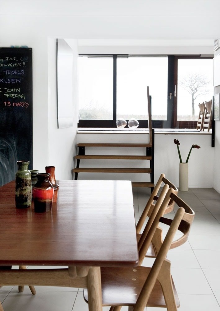 From the dining table overlooking the split level, the couple removed the wall between the kitchen and the split level room to let in more light.