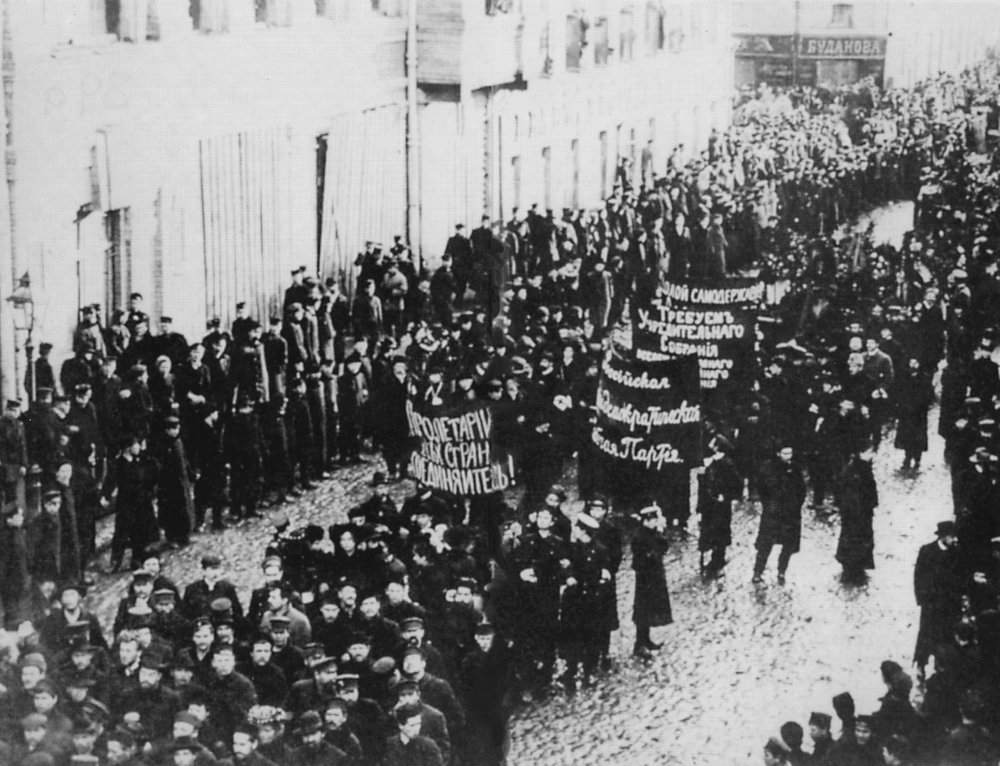 Workers-marching-through-the-streets-of-St.-Petersburg-during-the-1905-Russian-Revolution.-The-central-banner-reads-Proletarians-of-All-Countries.jpg