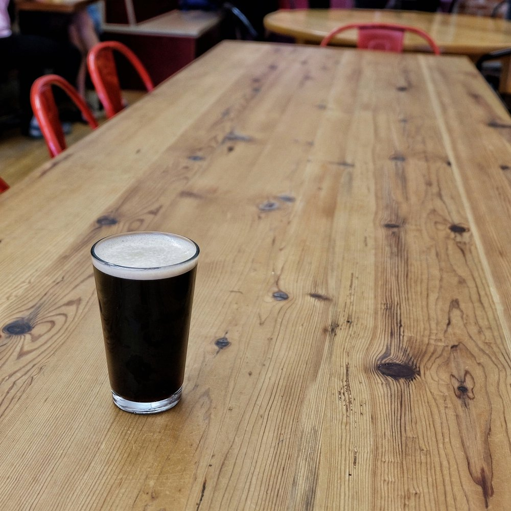A glass of nitro cold brew on a long wooden table