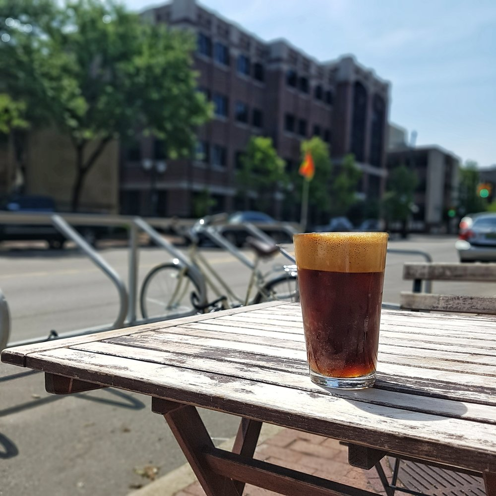 A glass of espresso tonic on a wooden table in the foreground, with a city scene in the background