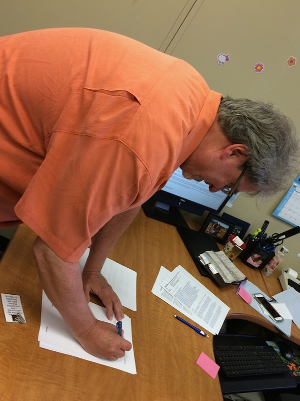 Mark Herrier, LTP president, signs documents at City Hall that allow LTP to purchase a deed of trust on the theater for $1. The Lompoc City Council voted to approve the sale of the deed Tuesday, Oct. 6.
