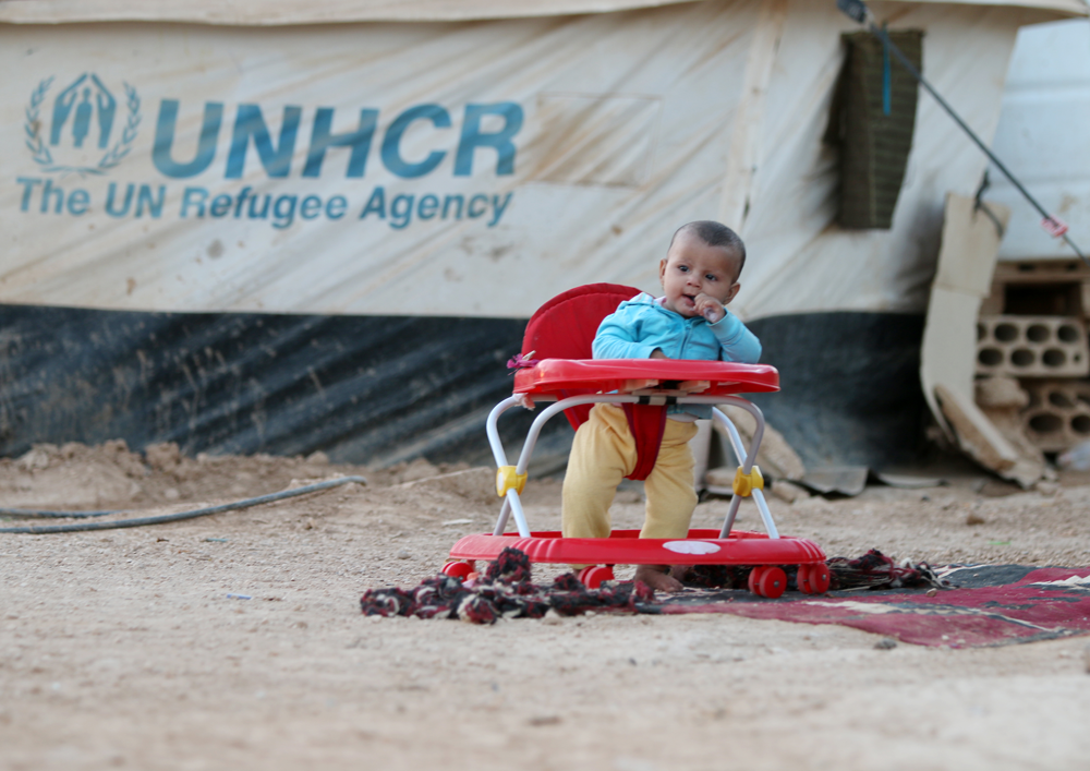 Syrian baby with UNHCR tent