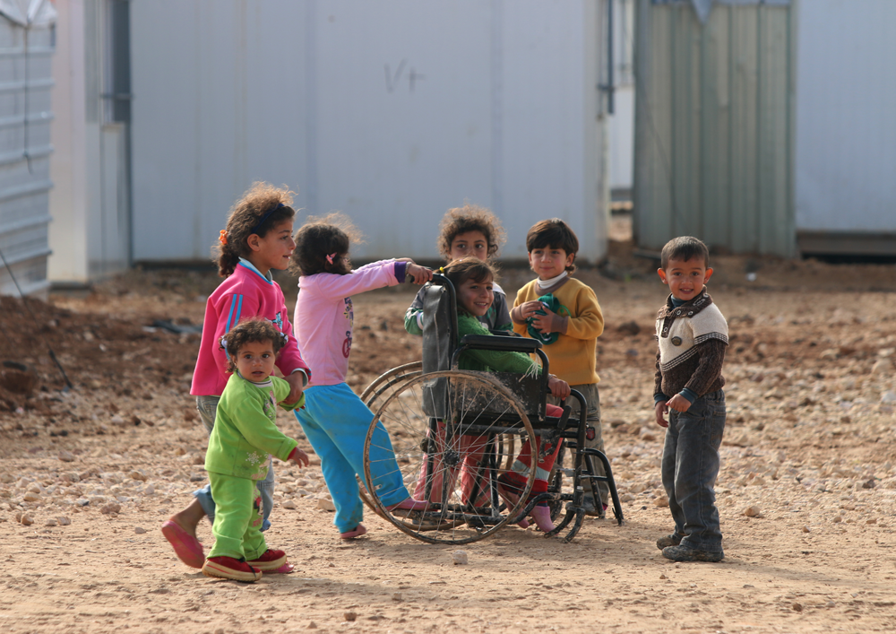 Injured syrian children play in refugee camp