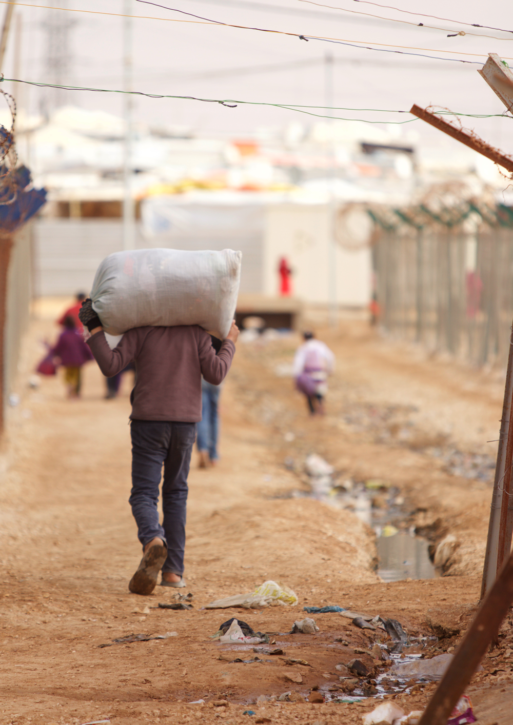 Syrian child refugee carrying load