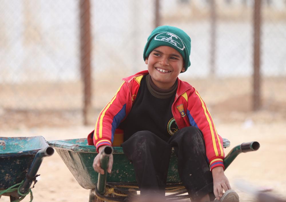 Syrian boy in wheelbarrow