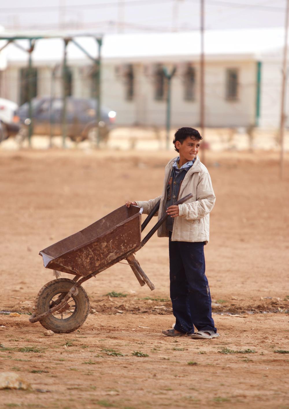 Syrian boy holding wheelbarrow