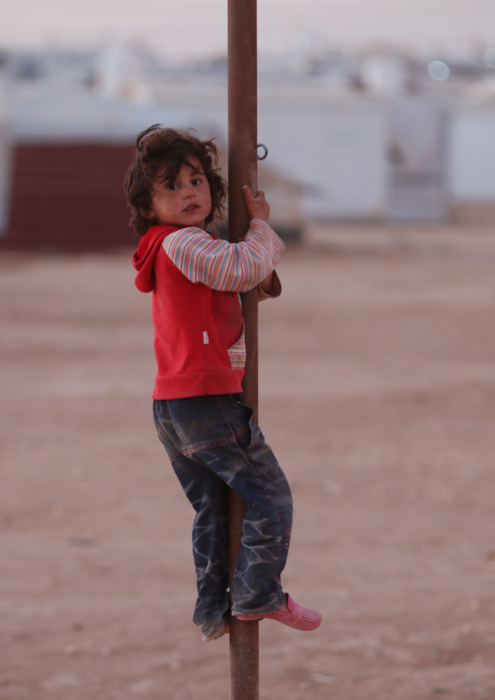 Syrian refugee child climbs pole