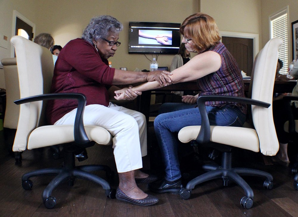 Participants in a recent stress busters class learn to administer hand massages which aid in stress relief for both caregivers and their loved one they are caring for.