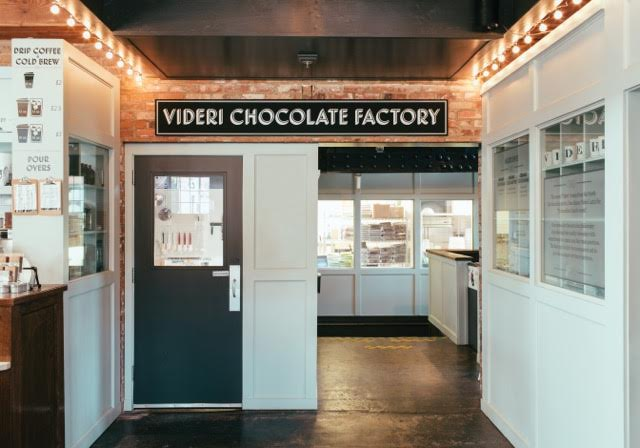 Inside the factory is an open door to the back area. The entire production space is viewable to the public. Signs and posters guide patrons on a self-guided tour that allows everybody to see the full operation happening. Transparency is a huge part of Videri's operation.
