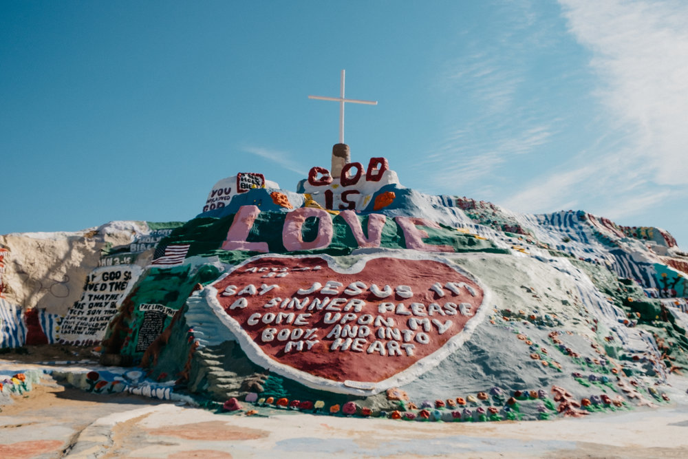 """Salvation Mountain is Leonard Knight's tribute to God and his gift to the world with its simple yet powerful message:  """"God Is Love.""""  Leonard's passion has lovingly created this brilliant """"outsider art """" masterpiece resplendent with not only biblical and religious scripture such as the Lord's Prayer, John 3:16, and the Sinner's Prayer, but also including flowers, trees, waterfalls, suns, bluebirds, and many other fascinating and colorful objects. - Taken from Official Website."""