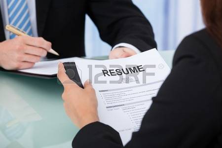 29323510-cropped-image-of-female-candidate-holding-resume-at-desk-during-interview.jpg