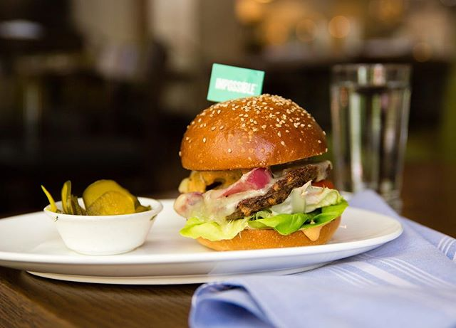 The impossibly delicious Impossible Burger ⚡️ We top ours with aged cheddar, roasted onions, remoulade, tomatoes, lettuce and b&b pickles.⠀ ⠀ #HeadwatersPDX #pdx #portland #downtownpdx #pdxdrinks #impossibleburger #pdxdining #pdxeats #pdxnow #eaterpdx #eater #portlandnw