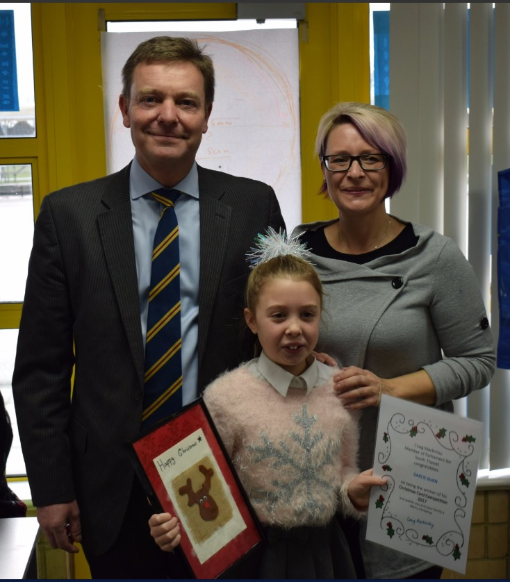 Craig presenting his Christmas Card 2017 Competition winner and Christ Church CE Junior School pupil, Darcie, with her winner's certificate