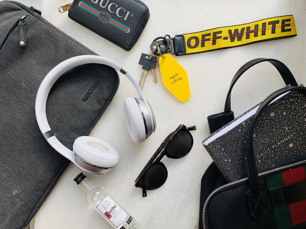 From left to right: Computer case by  Incase , wallet by  Gucci , headphones by  Beats by Dre , key ring by  Off-White ,  Ketel One Vodka , glasses by  Warby Parker , planner by  Urban Outfitters , backpack by  Gucci .