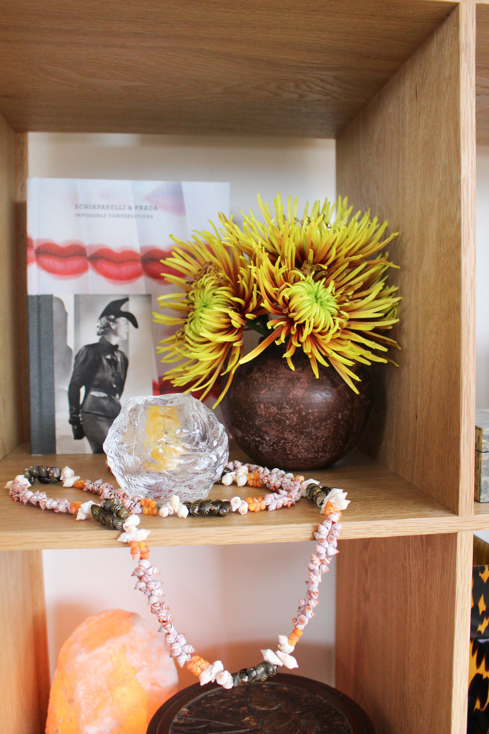 Classic Megan decor: everything on this shelf except the book and the flowers is from an op shop.  The book is  Impossible Conversations ; the flowers are chrysanthemums from Moore Wilsons