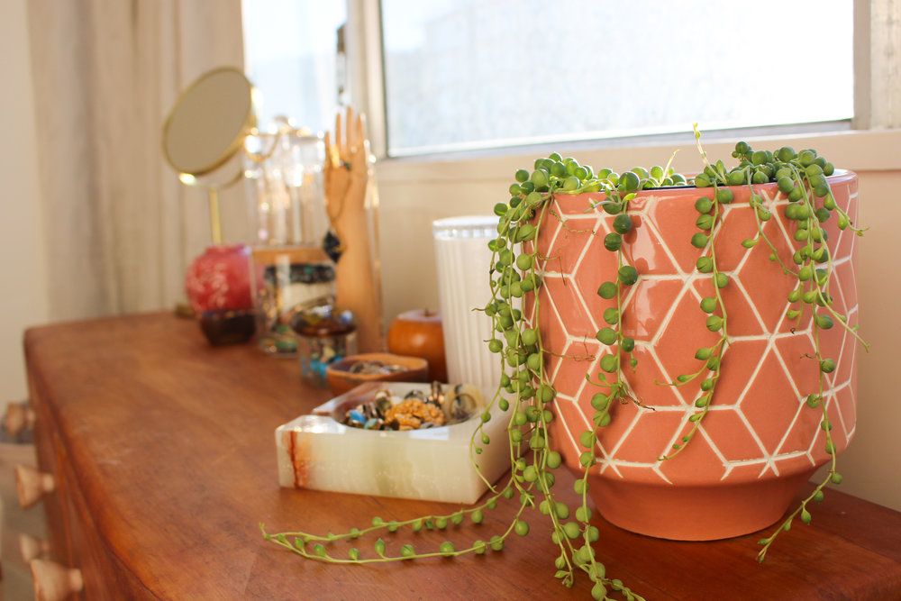 """I love a dressing table with plenty on display, and I also like to balance tall things at either end.  This string of pearls plants from Yvette, in a pot I picked up at Inhabit, was the perfect """"big bit"""" for the end of this and a great way to keep the pink going as a theme in the room.  Plus, needs minimal watering."""