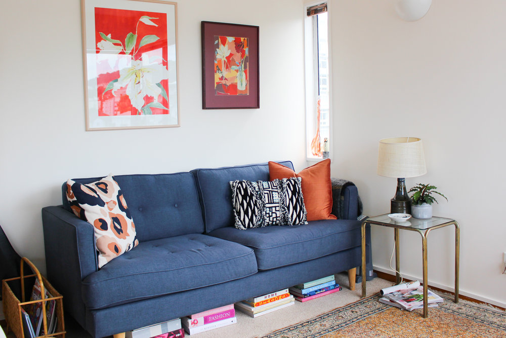 The most expensive thing in this photo is the $300 sofa (thanks again, Mum discount).  The lamp, side table, orange cushion, rug, art, and magazine holder are all secondhand.  Please note the attempt to find additional book storage by sliding various tomes under the couch…