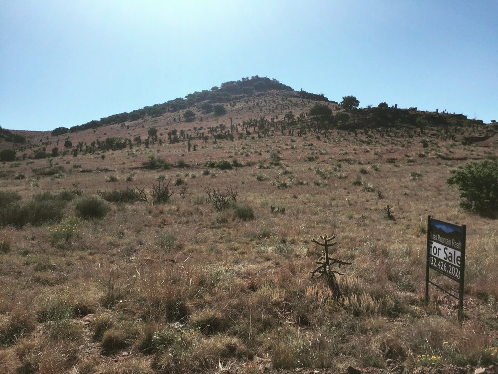 The 25 acre property extends up over the top of the hill and down the other side. The elevation at the top of the hill is about 5,700 ft.