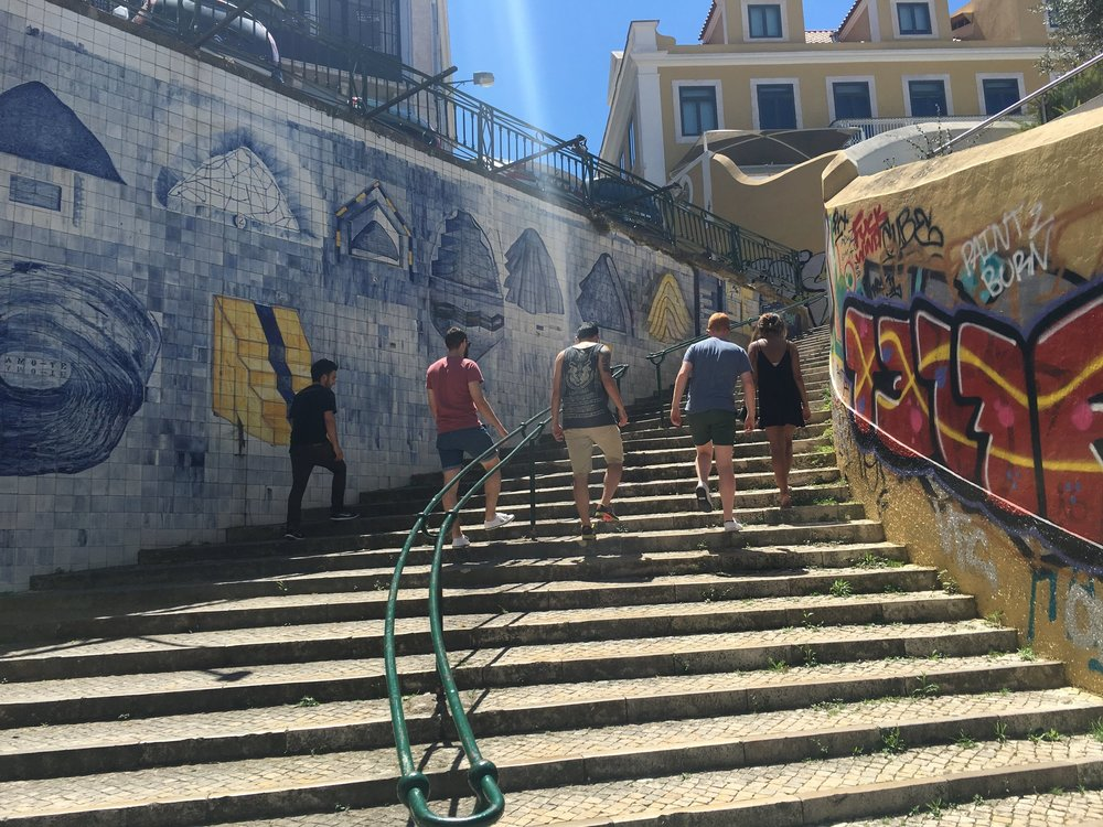 Classical meets modern. Some members of Guerrilla climb a staircase straddled by traditional tiles and trendy street art in Lisbon's Bairro Alto neighborhood. Photo by Justin Salhani.