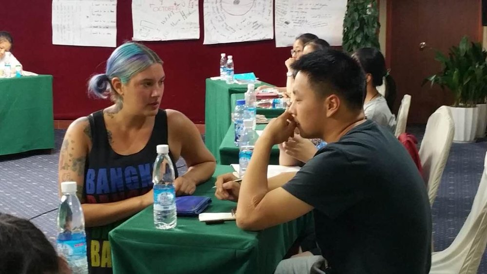 [Image Description: Lizbett is kneeling face to face with a student discussing their current project. The student is in a contemplative pose and holds a pen over his notebook in his other hand. There are other students seated at tables in the background.]