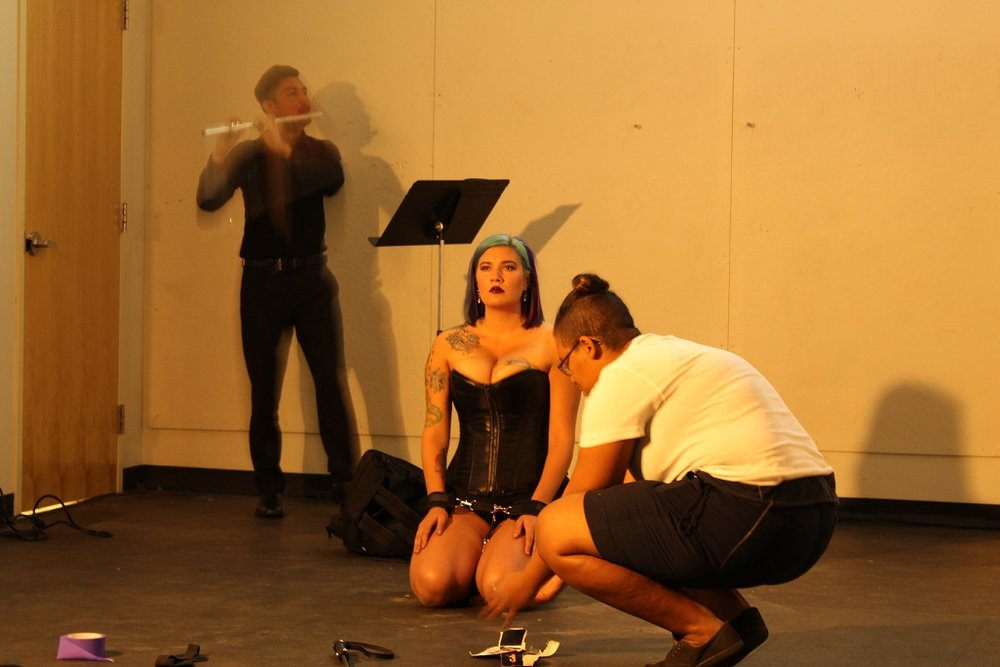 "[Image Description: This image is taken from a performance of ""La Syrinx"" during Arizona State University's Live Art Platform showcase on April 4, 2016. Lizbett is the center figure in the photo dressed in a black corset, she is sitting on her knees on a grey cement floor. Her hands are cuffed together and her face is blankly staring forward. In the foreground, a participant from the audience is kneeling with their side profile in view. They are picking up an object from the floor. In the background Chaz wears a dressy, all-black outfit as he plays his flute and reads the musical score on the music stand in front of him.]  photo credit: Angela Ellsworth"