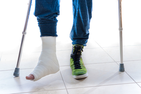58812946_S_man_cast_crutches_broken_foot_injury_sneaker.jpg
