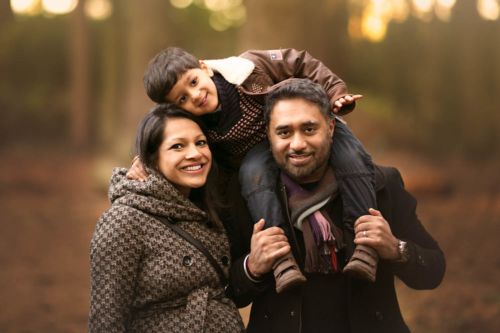 Family posing for portrait during an Autumn photoshoot at Rushmere Park, Bedfordshire