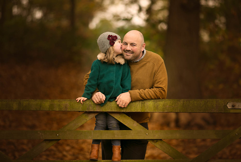 Father and dughter posing against a gate during an Autumn family photoshoot at Ampthill Park in Bedford.