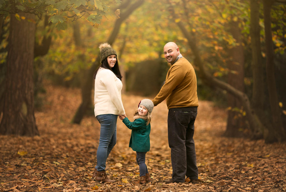 Mother, father and daughter looking over their shoulders in woodland duirng a family autumn photoshoot at Ampthill Park in Bedford.