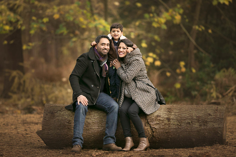 Family posing for portrait during autumn photoshoot at Rushmere Park, Bedfordshire