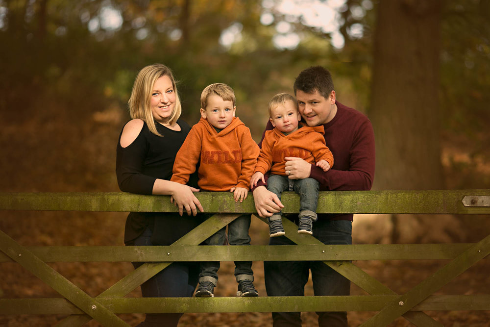 Family posing againgst a gate during family portrait session at Ampthill Park in Bedford.
