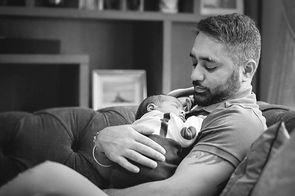 Father holding newborn baby son during a lifestyle photoshoot at client's home in Bedford.