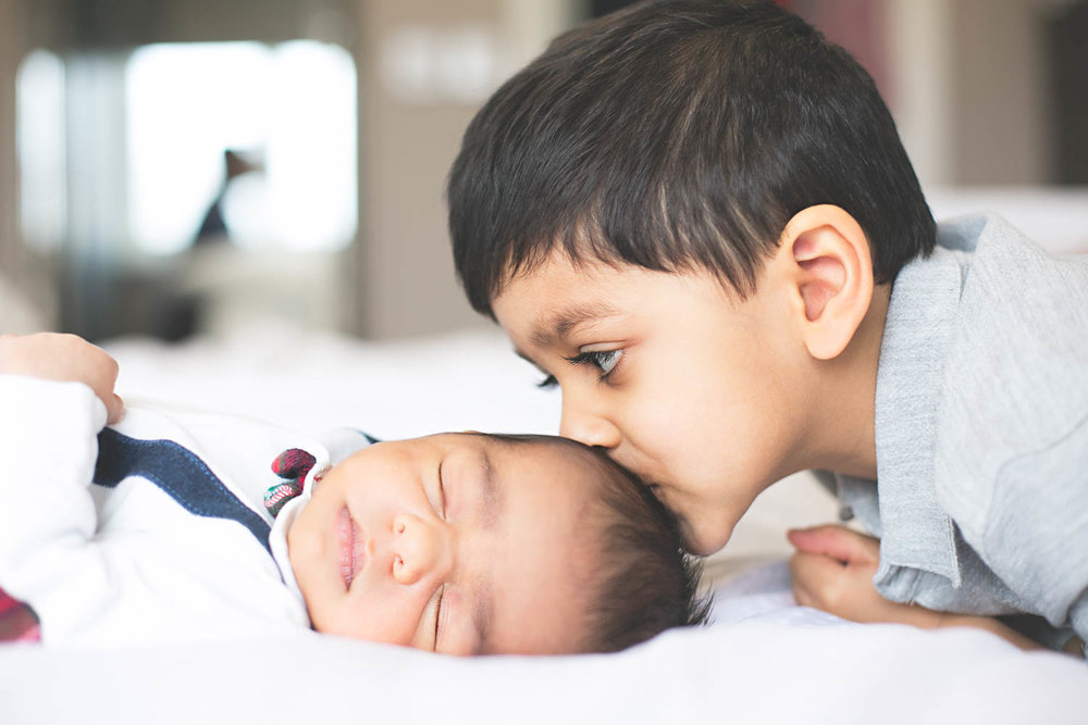 Brother kissing baby brother's head during a Newborn lifestyle photoshoot in Bedford.