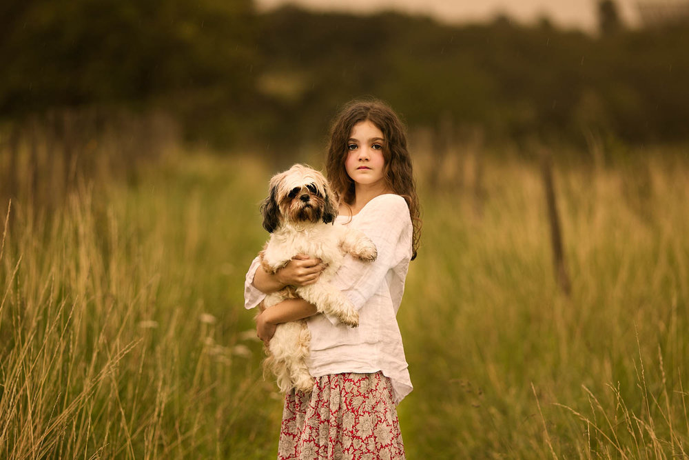 Young girl holding pet dog during a child portrait photography session.
