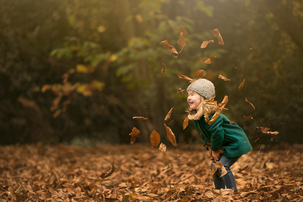 Young girl throwing leaves in Autumn family photoshoot at Amphtill Park in Bedford.