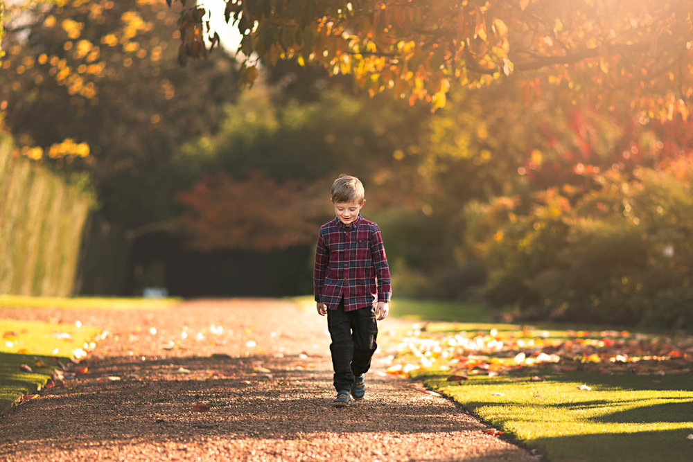 Young boy walking in the Autumn glow.