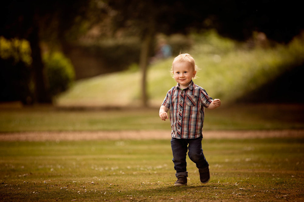 Toddler running during child photography session at Castle Ashby, Northampton.