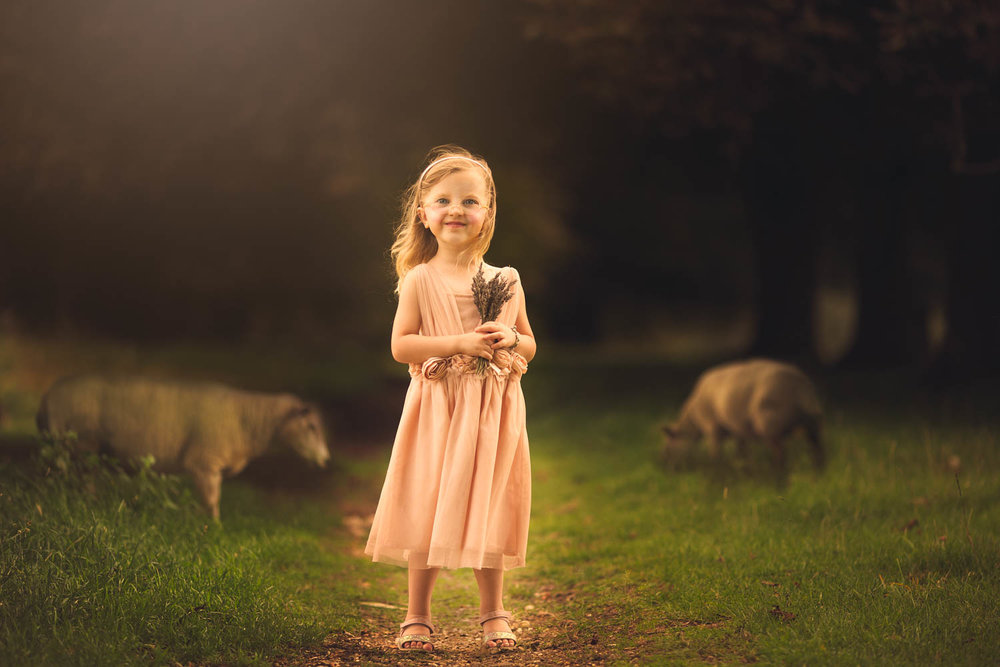 Child posing in field with sheep during a photography portrait session in Olney Buckinghamshire.