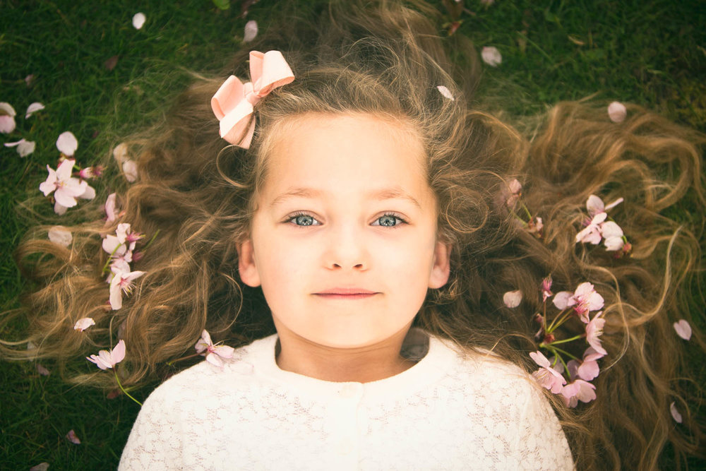 Young girl with blossom in her hair posing during Spring photoshoot.