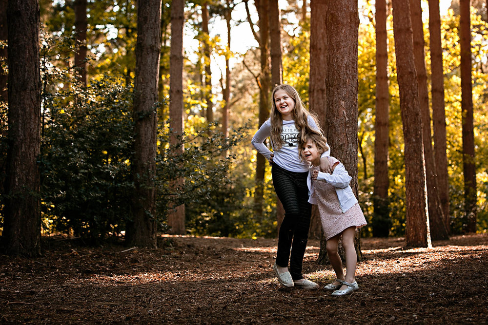 Sisters laughing during a child portrait photography session at Ampthill Park in Bedford.