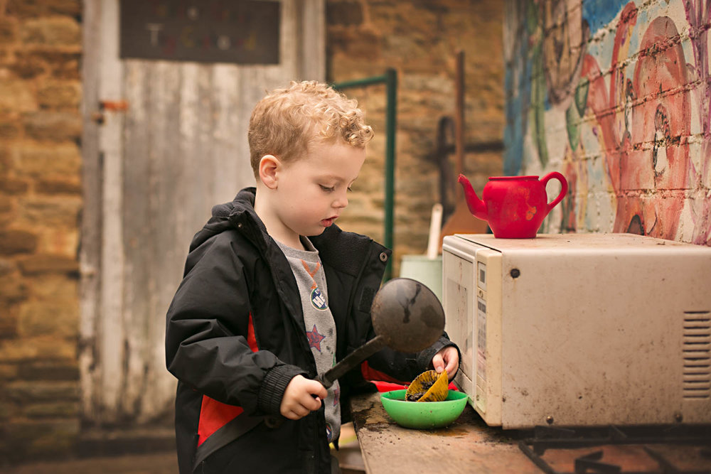 boy playing in outdoor kitchin during a preschool photoshoot in Turvey, Bedfordshire.