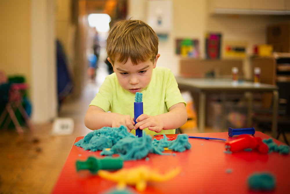 A portrait of a child at Turvey preschool playing with playdough during a Preschool photoshoot - Bedford.