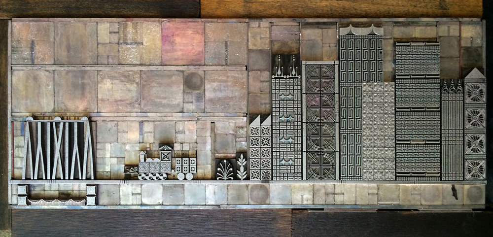 Letterpress metal type of cityscape and train